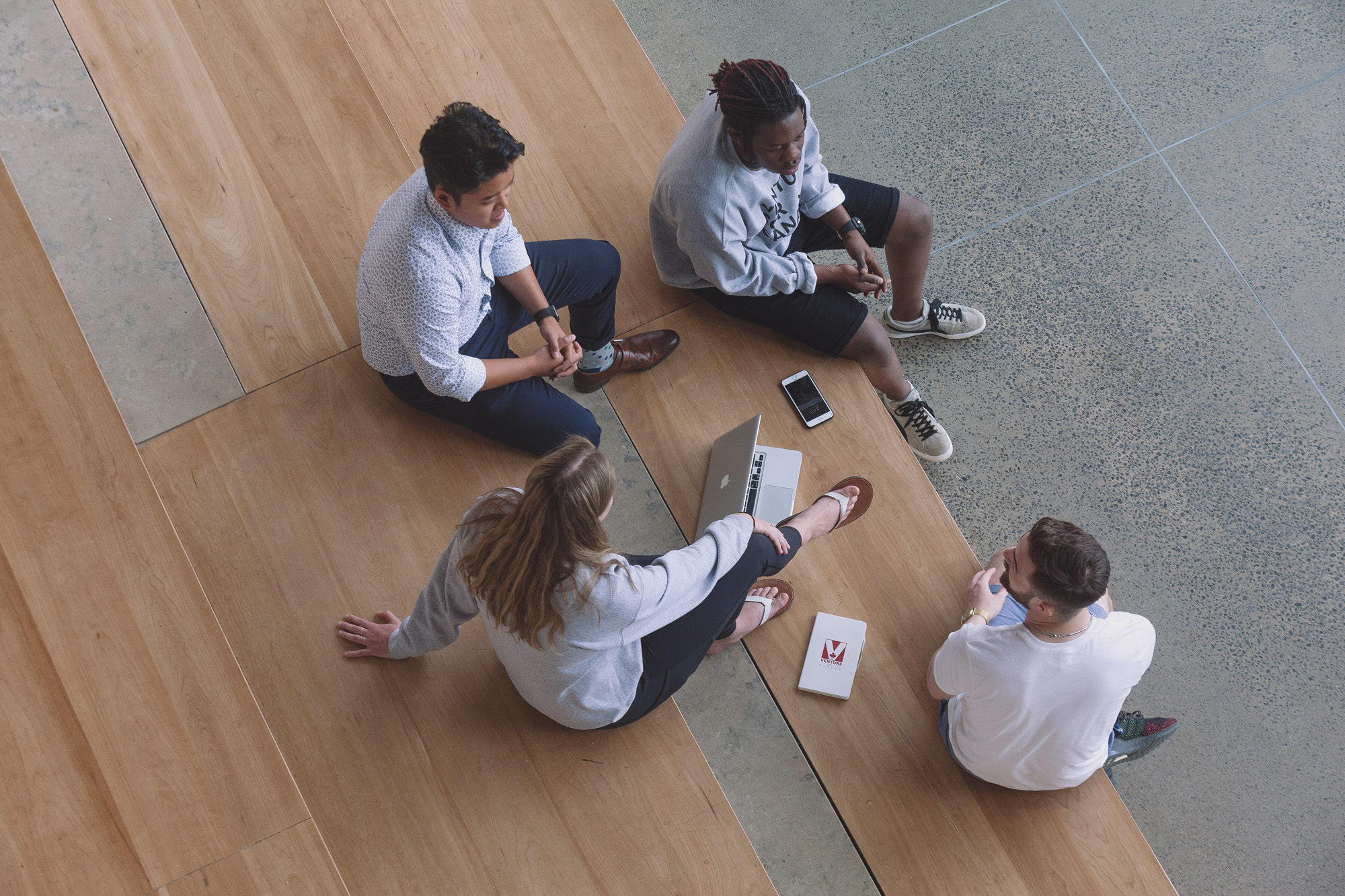A group of people discussing things sitting on a nice bench