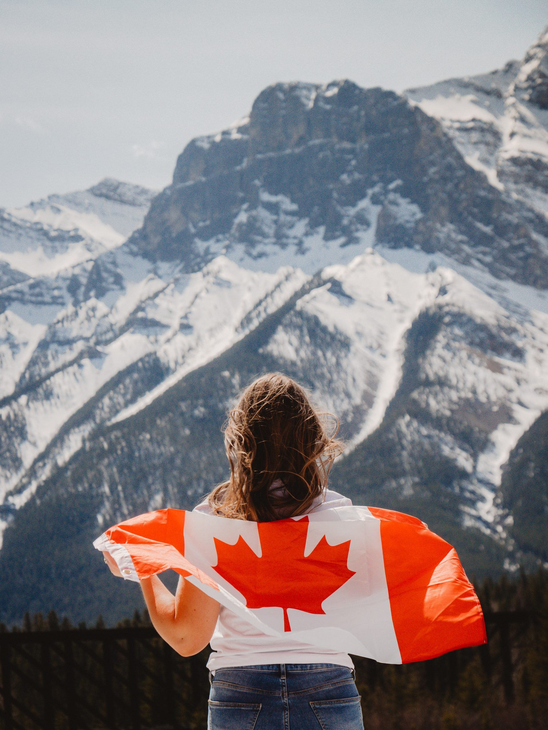 image of woman holding canadian flag looking at mountains